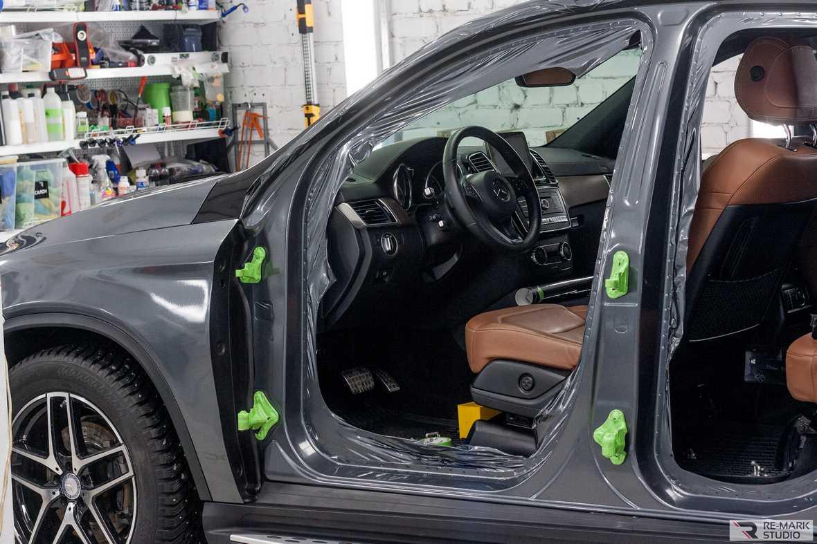 На фото промежуточный этап оклейки правой стороны автомобиля цельным куском виниловой пленки.