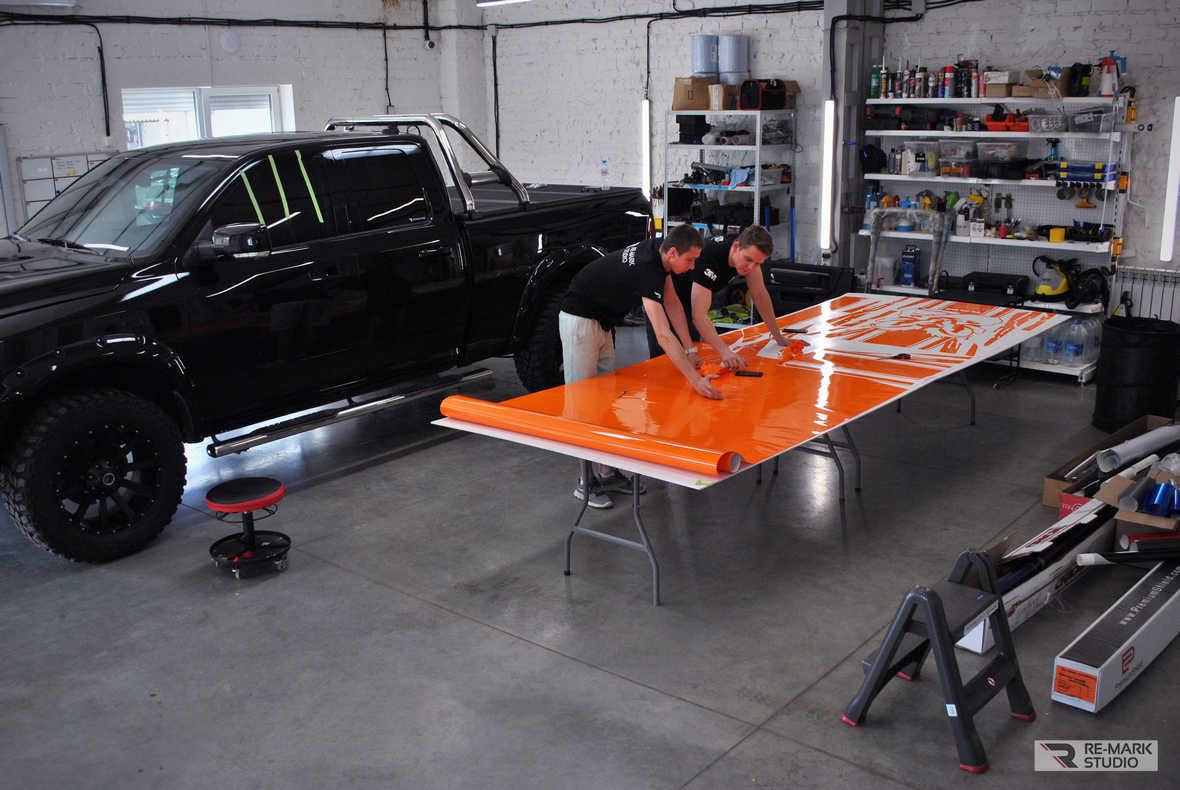 На фото рабочий процесс: разбор готового макета и поклейка виниловых фрагментов на Dodge RAM
