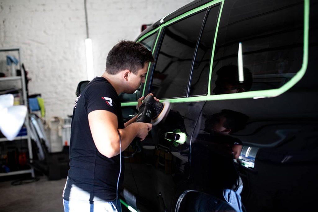 Смотреть на фото, как полируют машины в Воронеже. Мастер фирмы «Re-Mark Studio» делает зеркальную полировку двери автомобиля черного цвета.