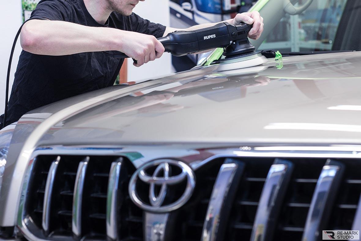 На фото мастер фирмы «Re-Mark Studio» полирует капот автомобиля Toyota с помощью полировочной машины Rupes.