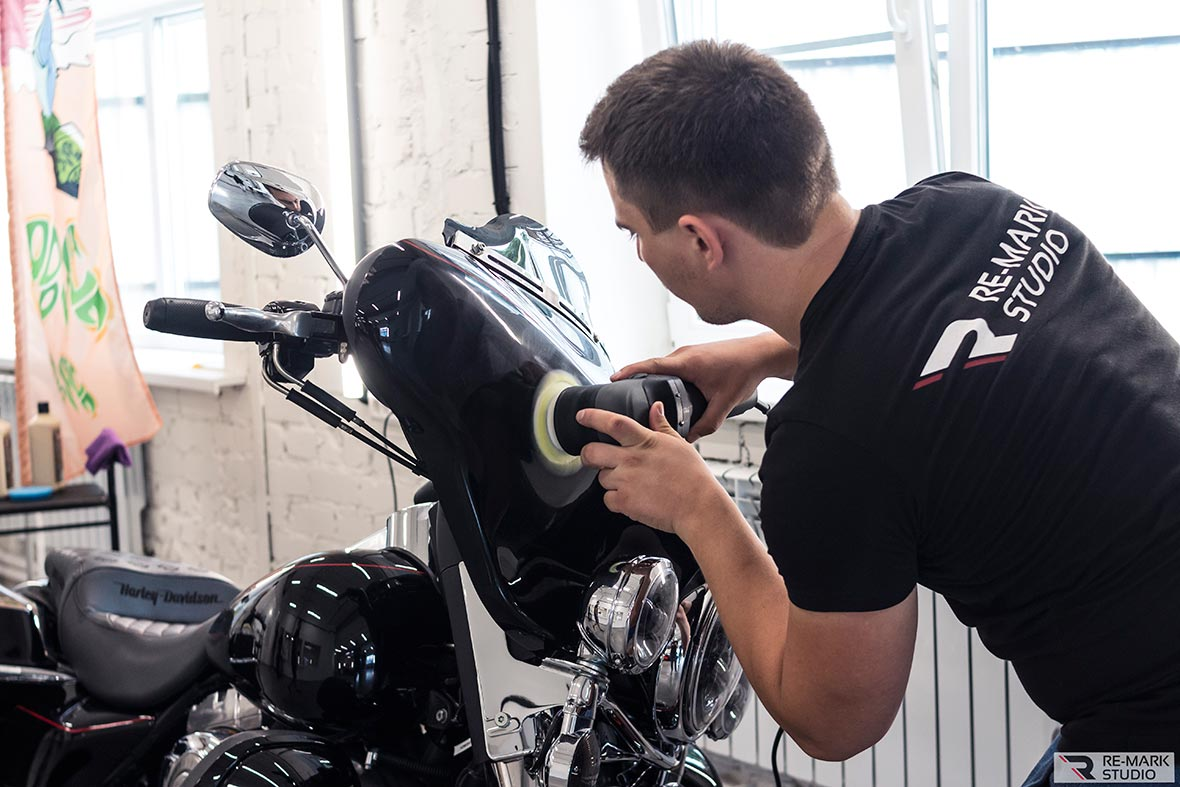 На фото мастер фирмы «Ре-Марк Студио» полирует ветрозащиту байка Харлей Девидсон.