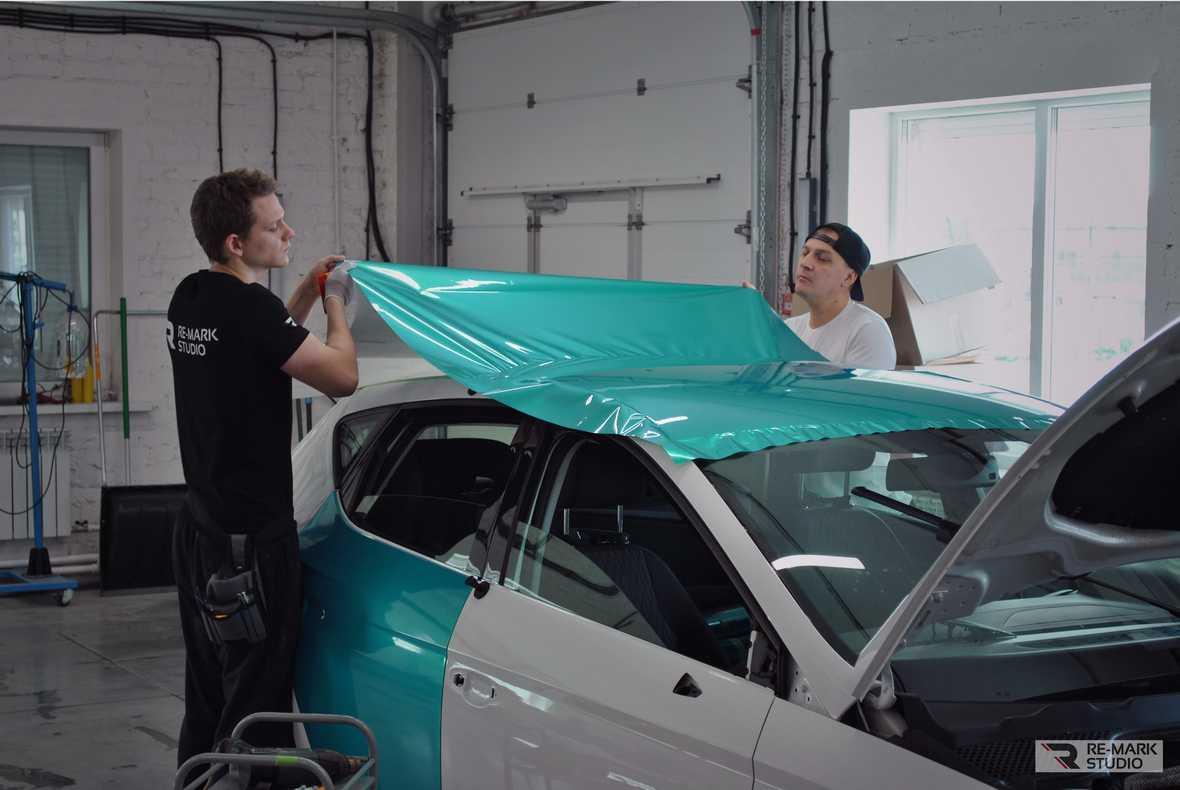 На фото специалисты «Re-Mark Studio» устанавливают винил на крышу автомобиля. Производится поклейка с полной заменой цвета.
