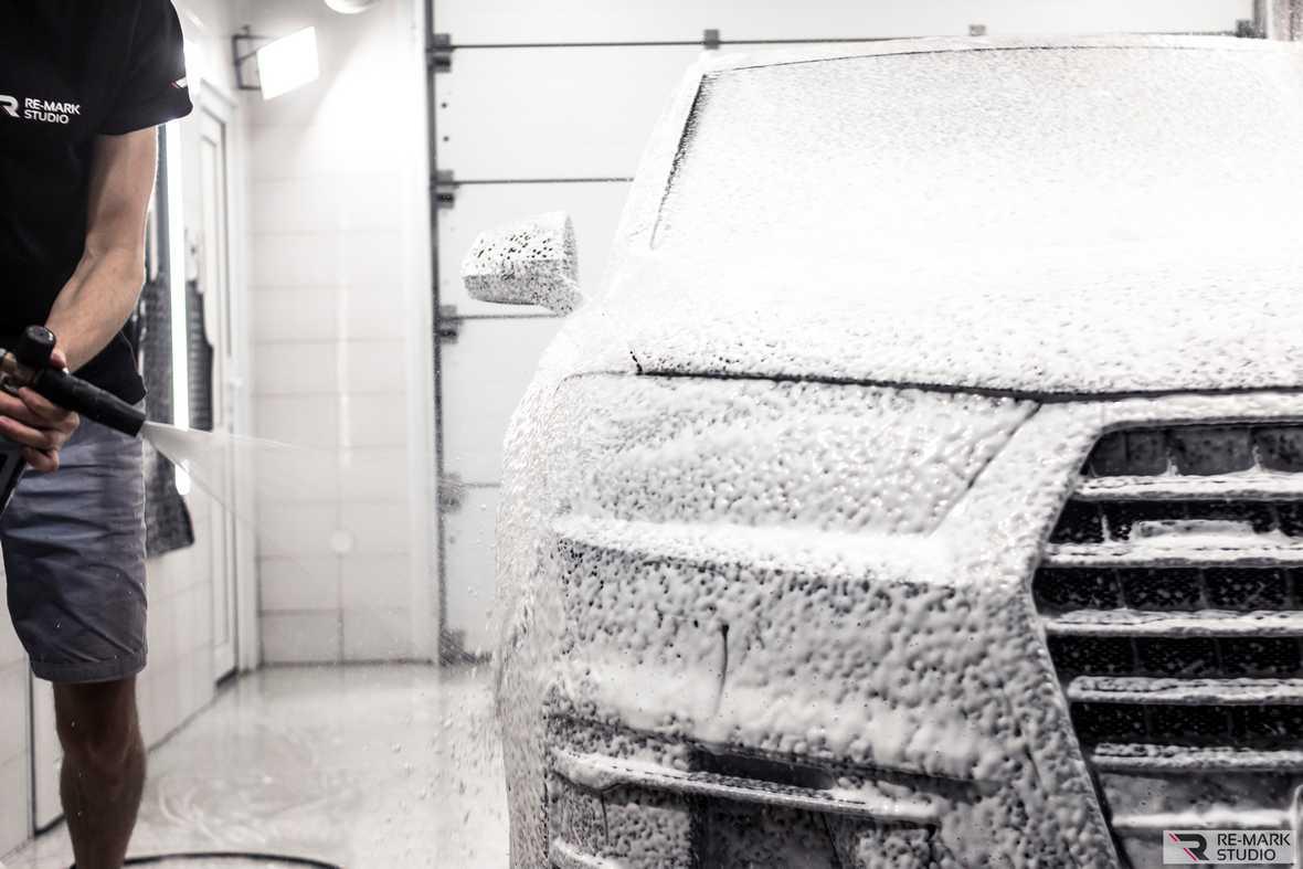 На фото этап керамической мойки – обработка кузова автомобиля эмульсией-очистителем.