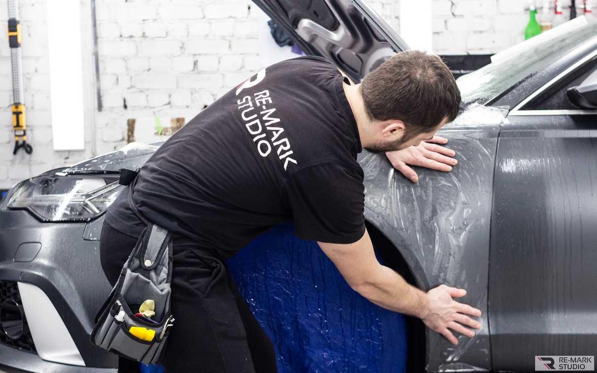 На фото мастер детейлинга «Re-Mark Studio» клеит на крыло автомобиля фрагмент пленки, вырезанный с помощью плоттера.