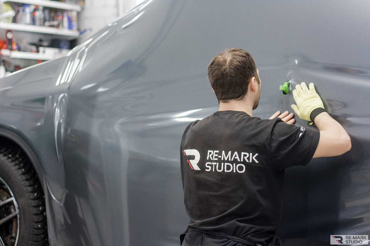 На фото мастер-технолог фирмы «Re-Mark Studio» производит первичный монтаж большого фрагмента пленки, закрывающего всю правую сторону автомобиля.