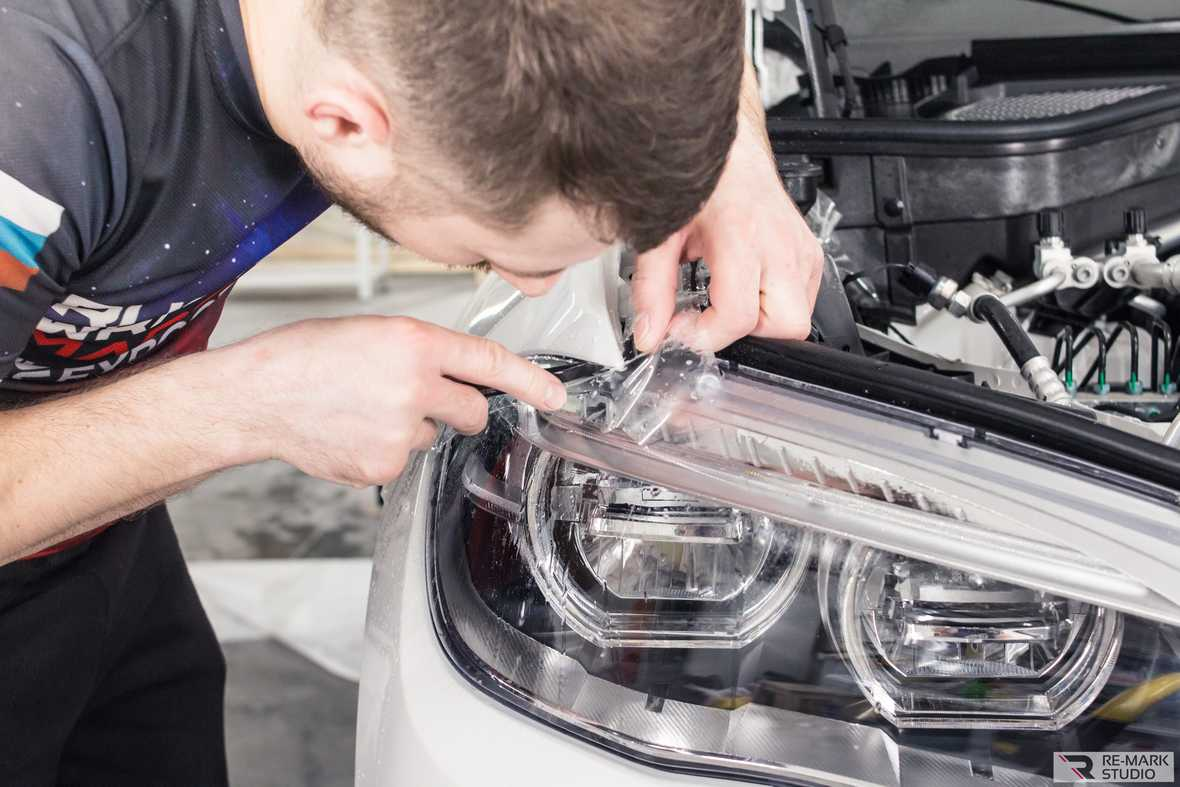 На фото мастер заклеивает полиуретановой пленкой фару автомобиля.