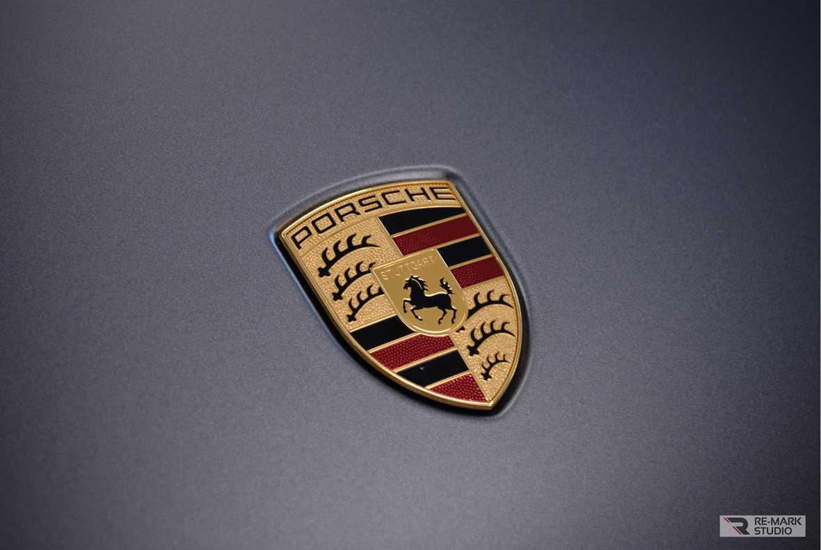 На фото шильдик на капоте Porsche Cayenne после полной оклейки автовинилом.