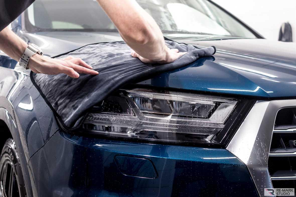 На фото специалист ателье «Re-Mark Studio» протирает капот у автомобиля Audi