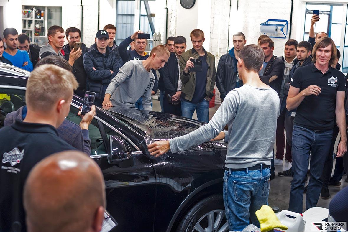 На фото поклейка антигравийной пленки 3M. Специалисты под управлением инструктора устанавливают пленку на капот автомобиля.