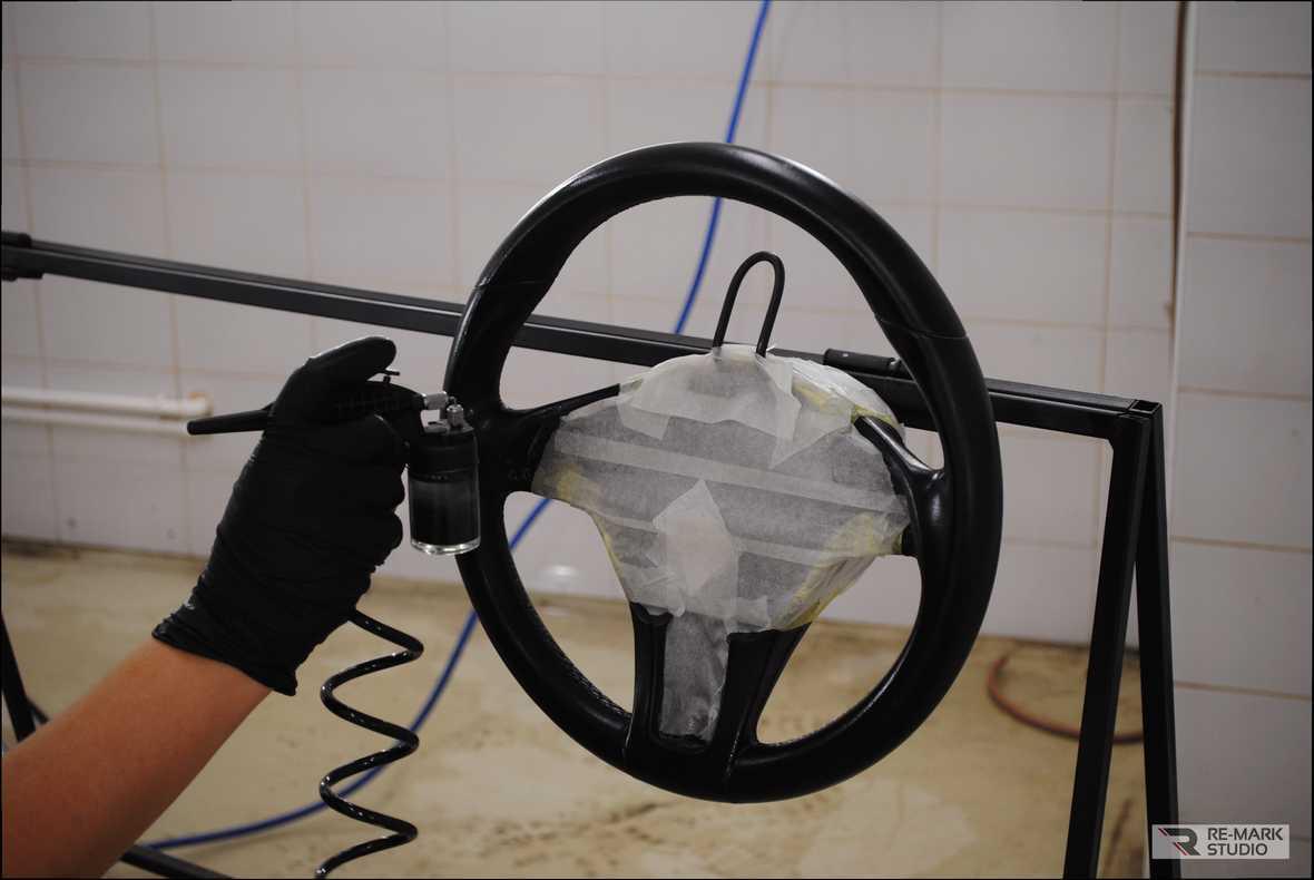 На фото мастер-технолог фирмы «Re-Mark Studio» выполняет окрашивание кожи на руле с помощью аэрографа.