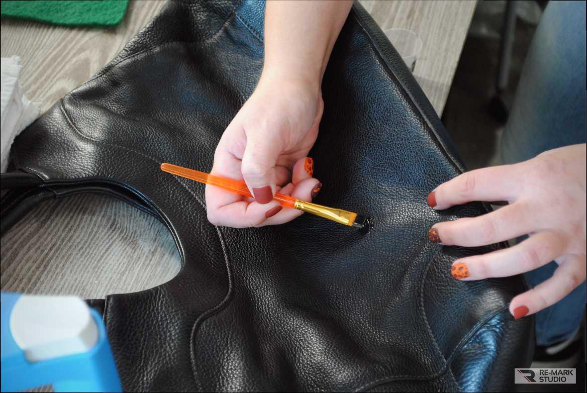 На фото мастер-технолог «Re-Mark Studio» убирает царапины на кожаной сумке.