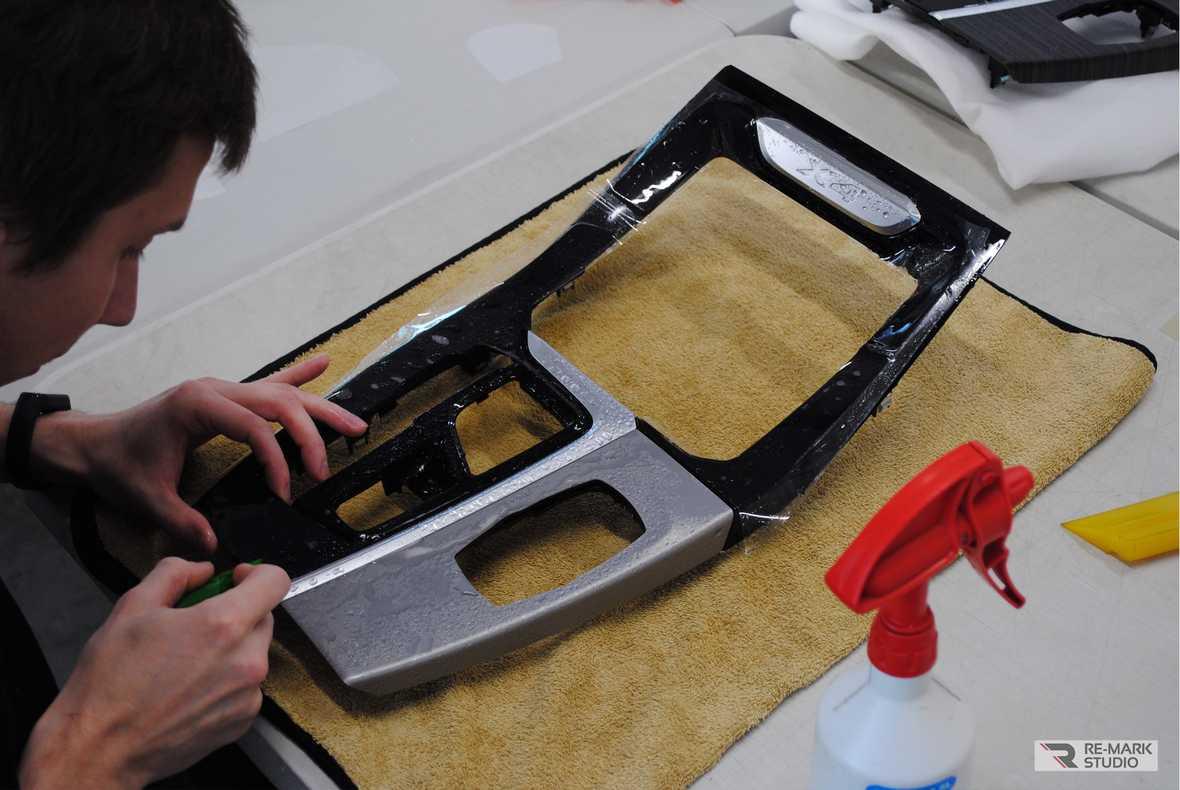 Смотреть на фото, как мастер оклеивает части салона BMW x4 полиуретановой пленкой.