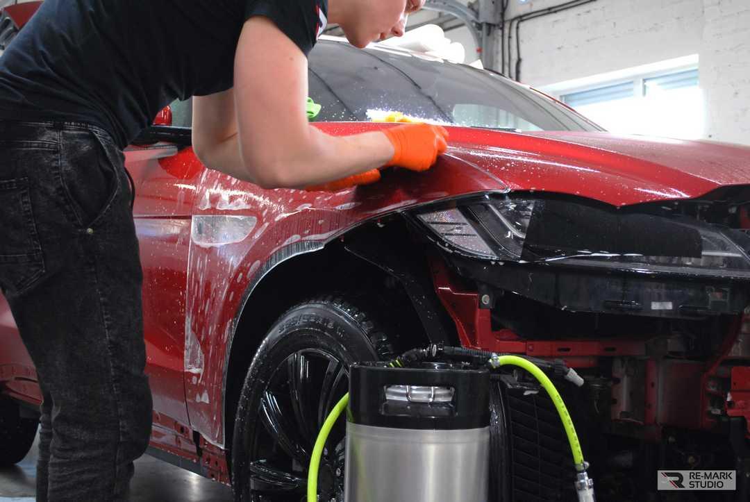 Смотреть на фото процесс монтажа матовой антигравийной пленки на крыло автомобиля Jaguar F-pace.