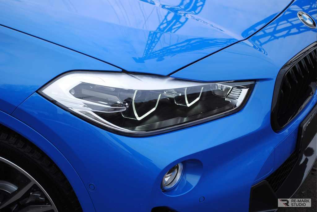 Смотреть на фото крупный план передней части автомобиля BMW X2 после установки на зоны риска антигравийной пленки PremiumShield.