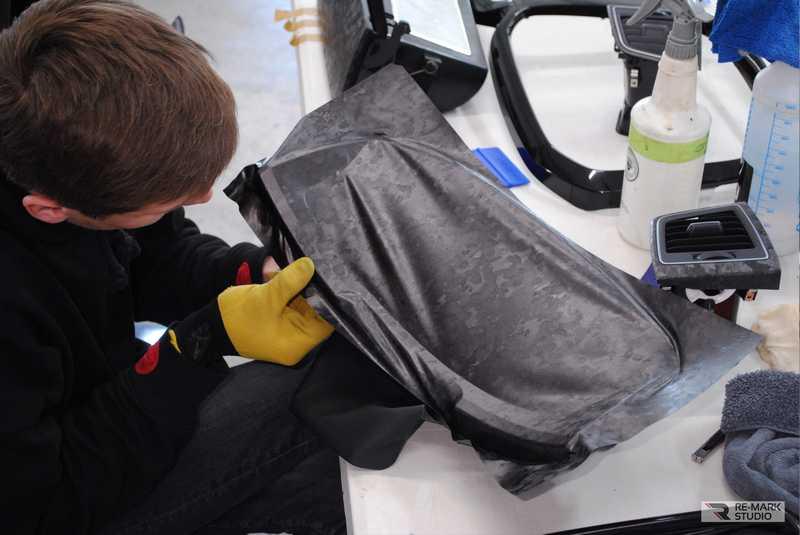 Смотреть на фото процесс оклейки элемента консоли автомобиля Фольксваген виниловой пленкой Hexis «Кованый карбон».