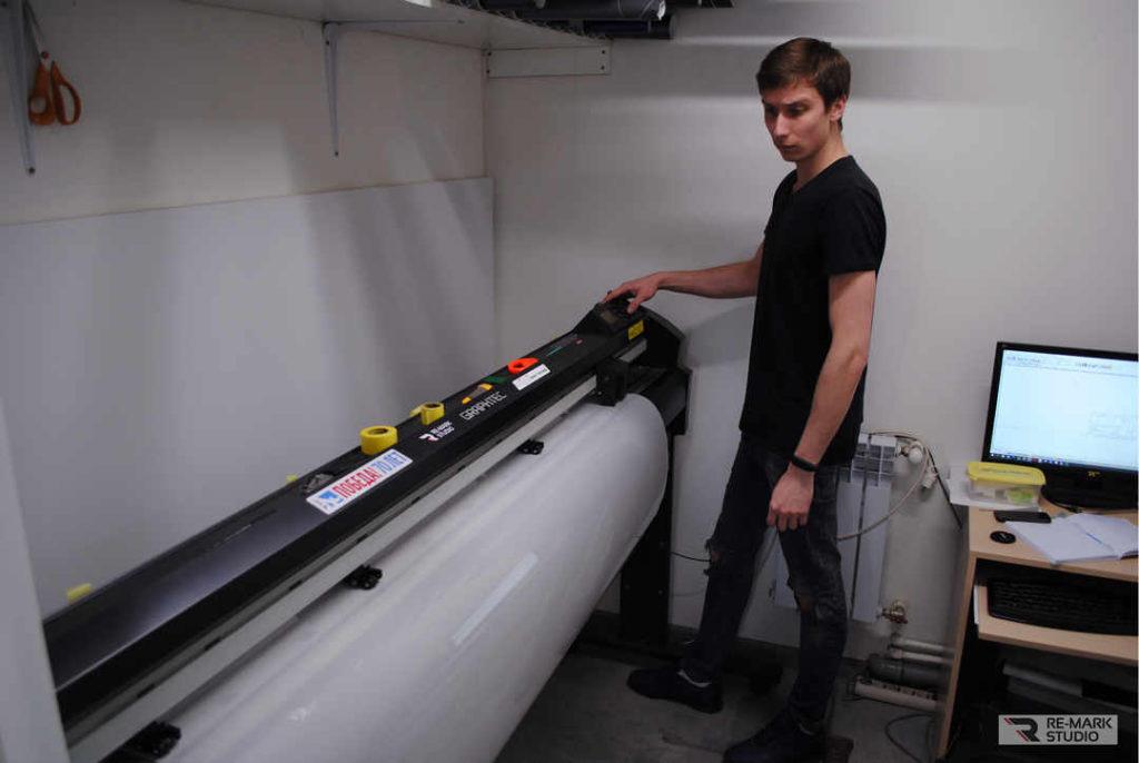 На фото мастер «Re-Mark Studio» за работой. Выполняется нарезка полиуретановой пленки PremiumShield на плоттере.