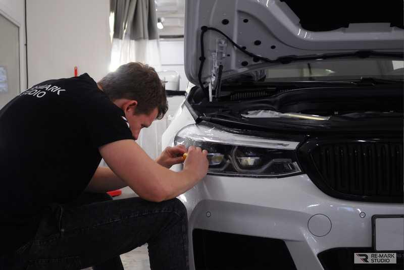 Смотреть на фото как мастер фирмы RE-MARK STUDIO бронирует фары автомобиля пленкой PremiumShield.
