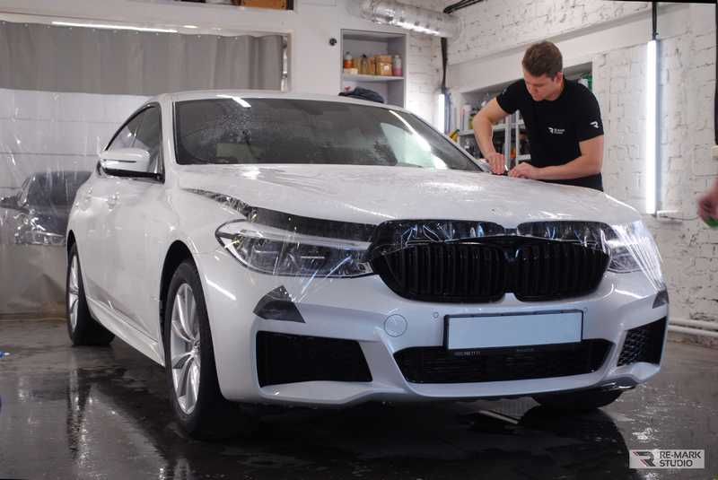 Смотреть на фото процесс оклейки капота автомобиля BMW 6GT антигравийной пленкой PremiumShield.