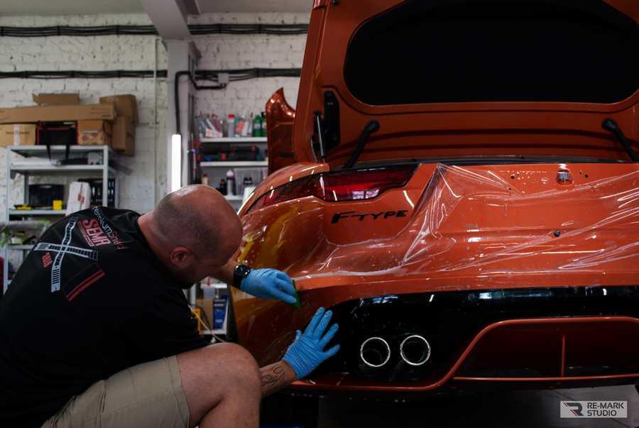 Смотреть на фото работу мастера фирмы RE-Mark Studio. Процесс оклейки заднего бампера автомобиля Jaguar F-Type.