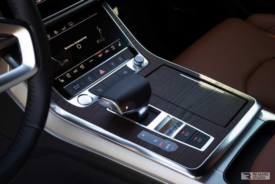 Смотреть на фото консоль Audi Q8 после оклейки декоративной пленкой под темное дерево.