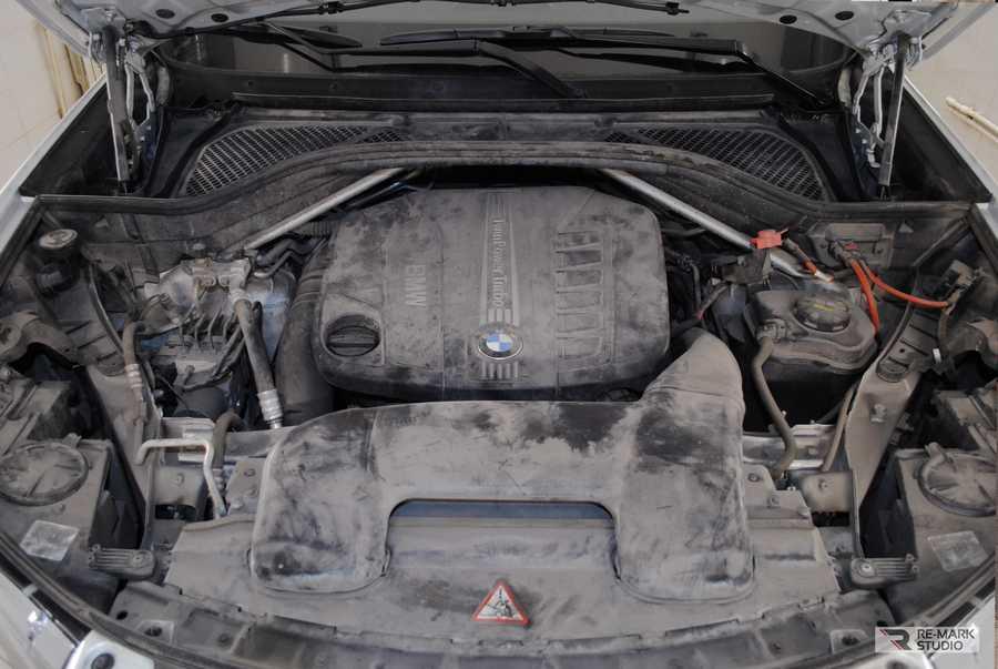 Смотреть на фото грязный мотор BMW X6 до мойки и химчистки.