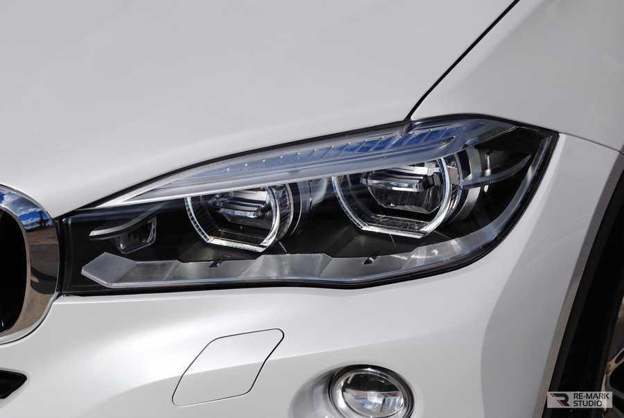 Смотреть на фото фару BMW X6 после оклейки полиуретановой защитной пленкой.