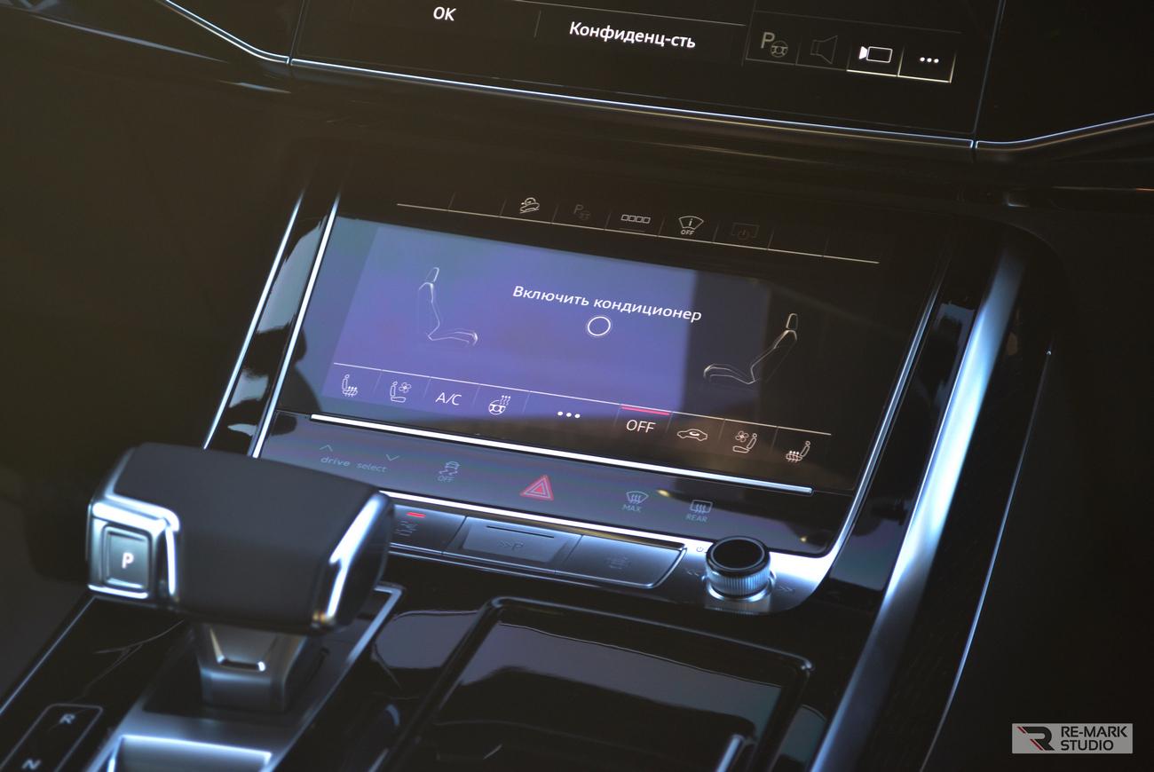 Смотреть на фото глянцевые элементы салона автомобиля Audi Q8 после оклейки защитной пленкой.
