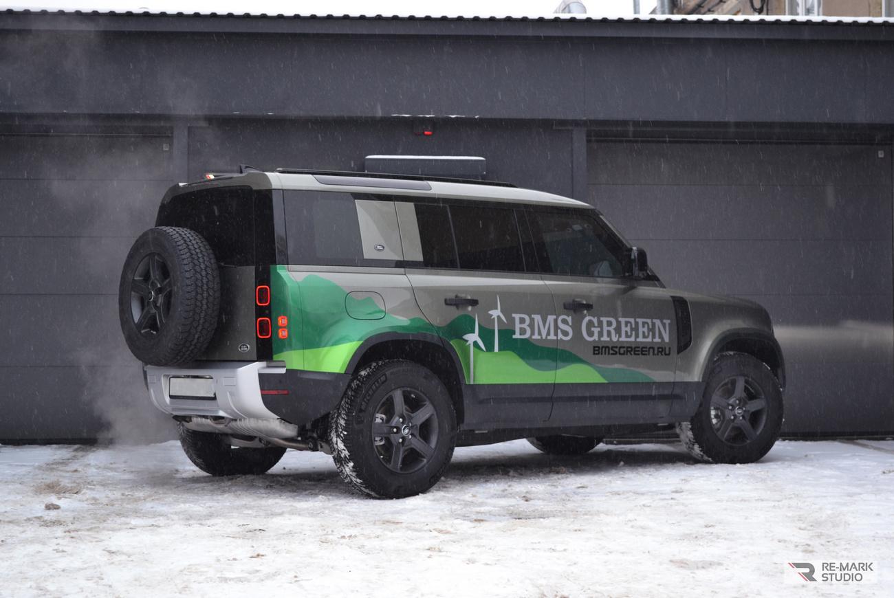 Смотреть на фото Land Rover Defender с брендовыми надписями на бортах.