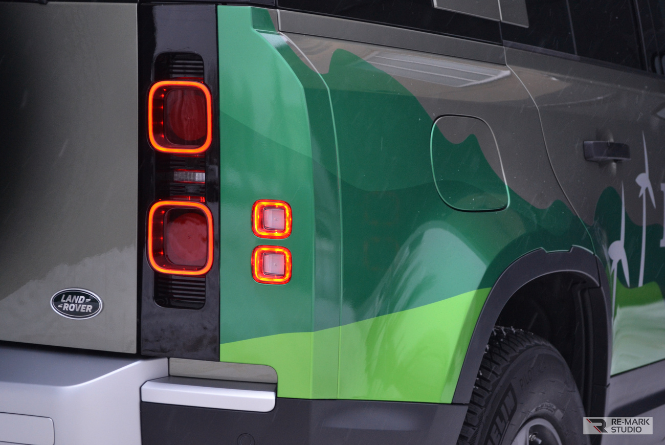 Смотреть на фото крупным планом автомобиль Land Rover Defender после оклейки цветным литым винилом. Работу выполнили мастера фирмы RE-MARK STUDIO.