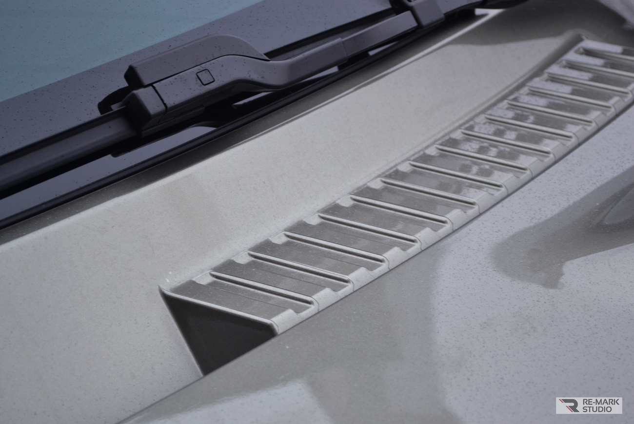 Смотреть на фото крупным планом элемент автомобиля Land Rover Defender после оклейки антигравийной пленкой под плоттер.