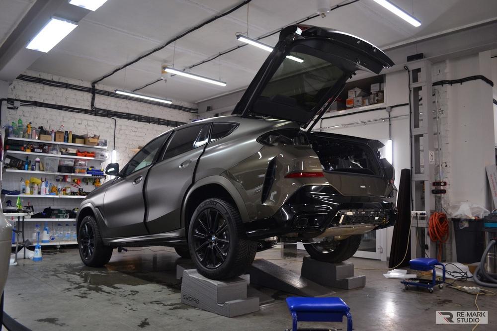 Смотреть на фото процесс оклейки автомобиля BMW матовой антигравийной пленкой.