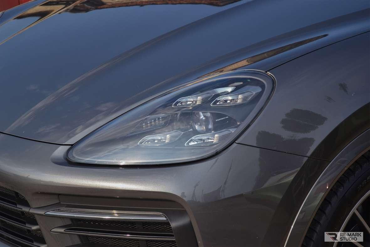 Смотреть на фото капот, бампер, фару автомобиля Порш Кайенн крупным планом. На машину нанесена керамика KRYTEX.